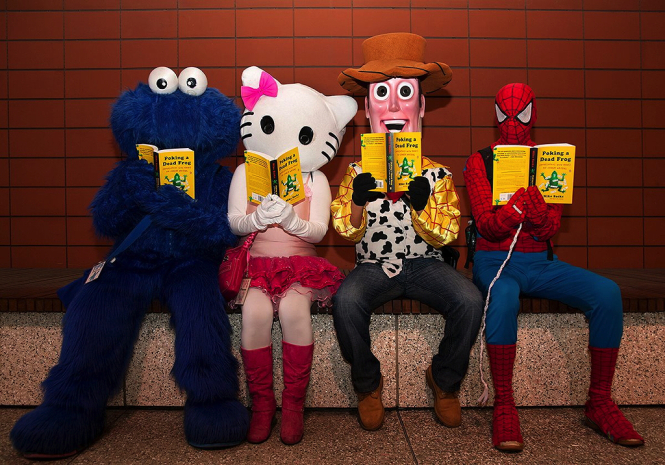 Four costumed characters—Cookie Monster, Hello Kitty, Woody from Toy Story, and Spider-Man—reading Mike Sacks's book Poking a Dead Frog. Photo by Chris George.